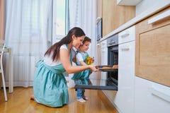 愉快的家庭在厨房里 愉快的妈妈教女儿烹调 免版税库存照片