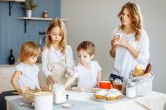愉快的家庭在厨房里 母亲和她逗人喜爱的孩子烹调曲奇饼 免版税库存照片