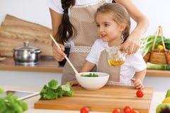 愉快的家庭在厨房里 烹调鲜美breakfest新鲜的沙拉的母亲和儿童女儿 一点帮手切  免版税库存照片