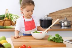 愉快的家庭在厨房里 烹调鲜美breakfest新鲜的沙拉的母亲和儿童女儿 一点帮手切  库存照片