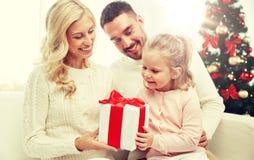 愉快的家庭在家与圣诞节礼物盒 免版税图库摄影