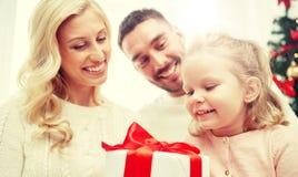 愉快的家庭在家与圣诞节礼物盒 免版税库存照片