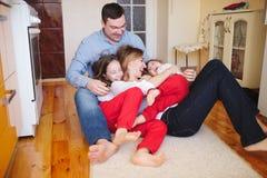 愉快的家庭在家在地板上 免版税库存照片