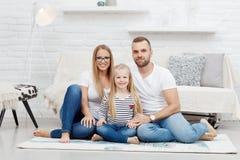 愉快的家庭在家坐地板 免版税库存图片