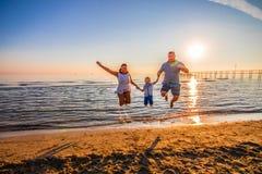 愉快的家庭在日落光的岸跳 免版税库存图片