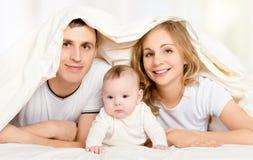 愉快的家庭在毯子下的床上 图库摄影