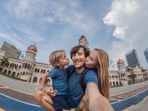 愉快的家庭在独立报广场和苏丹阿卜杜勒萨玛德大厦背景的背景做selfie  旅行 免版税库存图片
