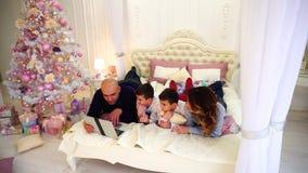 愉快的家庭在膝上型计算机后一起花费时间,说谎在床上在有圣诞树和礼物的明亮的卧室 股票录像