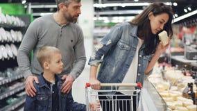 愉快的家庭在超级市场,妇女选择乳酪采取片断,看它并且嗅到它,然后她的丈夫 股票录像