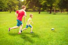 愉快的家庭在晴朗的公园踢橄榄球 库存图片