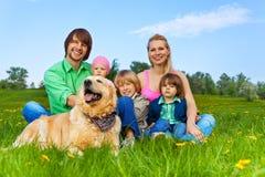 愉快的家庭坐与狗的绿草 免版税库存照片