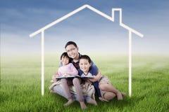 愉快的家庭坐在房子标志下在领域 库存图片