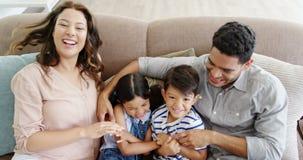 愉快的家庭坐沙发和获得乐趣在客厅 股票录像