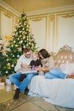 愉快的家庭坐沙发在圣诞树附近 免版税库存照片