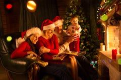 愉快的家庭坐沙发,当读在圣诞节的一本故事书装饰了室时 免版税库存图片