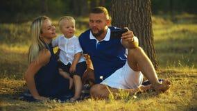 愉快的家庭坐草并且做着与婴孩的selfie在日落在公园 父母拍照片 股票录像