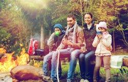 愉快的家庭坐长凳在阵营火 免版税库存照片