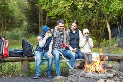 愉快的家庭坐长凳在阵营火 免版税库存图片