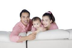 愉快的家庭坐长沙发 免版税库存照片