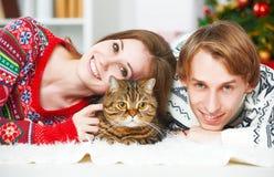 愉快的家庭夫妇和猫在圣诞节在家 免版税库存图片