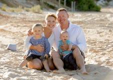 愉快的家庭夫妇坐与男婴儿子和女儿的海滩沙子 免版税图库摄影