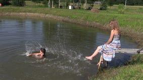 愉快的家庭女儿女孩飞溅池塘水和怀孕的母亲 股票录像