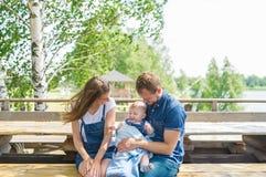 愉快的家庭好时光坐一个长木凳户外 父亲、母亲和小儿子 库存图片