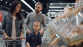 愉快的家庭妈妈、爸爸和逗人喜爱的孩子在大超级市场选择食物,指向塑胶容器,谈话 股票录像