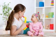 愉快的家庭妈妈和小女儿演奏音乐玩具 免版税库存照片