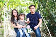 愉快的家庭妈妈母亲女儿父亲parenters在公园微笑快乐的棒棒糖的夏天演奏并且获得乐趣在女孩手上本质上 免版税库存照片