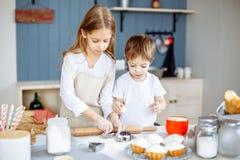 愉快的家庭姐妹和兄弟烘烤曲奇饼在厨房里 库存照片