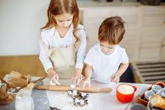 愉快的家庭姐妹和兄弟烘烤曲奇饼在厨房里 免版税图库摄影