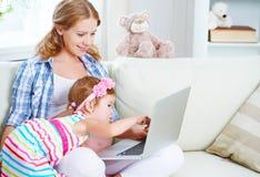 愉快的家庭孕妇和孩子有膝上型计算机的在家 免版税库存照片