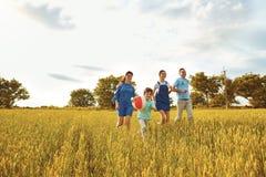愉快的家庭微笑的跑在领域本质上 库存图片
