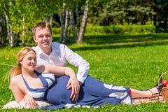 愉快的家庭怀孕的夫妇在一个夏天停放 免版税库存照片