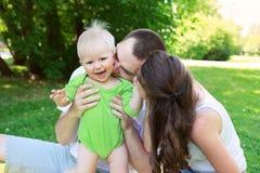 愉快的家庭户外妈咪和爸爸抱着并且亲吻婴孩 免版税库存照片