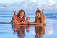 愉快的家庭旅行-父亲,母亲,日落海滩的小儿子 免版税库存图片