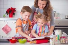 愉快的家庭曲奇饼为圣诞前夕做准备 免版税库存照片