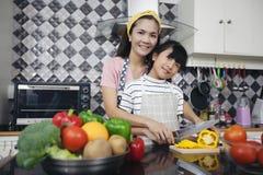愉快的家庭有烹调衣服的爸爸、妈妈和他们的小女儿 库存照片