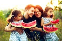 愉快的家庭有野餐在绿色庭院 吃西瓜的微笑的和笑的人民 健康食品概念 喜爱是两次曝光变了得极度兴奋她一个假装s显示姐妹姐妹孪生 图库摄影