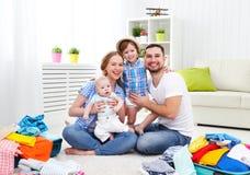 愉快的家庭母亲、父亲和两个孩子包装了手提箱fo 免版税库存图片