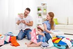 愉快的家庭母亲、父亲和两个孩子包装了手提箱fo 免版税库存照片