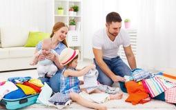 愉快的家庭母亲、父亲和两个孩子包装了手提箱fo 免版税图库摄影
