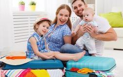 愉快的家庭母亲、父亲和两个孩子包装了手提箱fo 库存照片