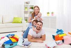 愉快的家庭母亲、父亲和两个孩子包装了手提箱fo 图库摄影