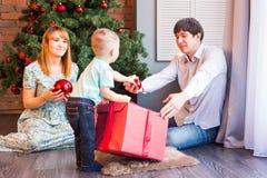 愉快的家庭母亲、父亲和使用在冬天的婴孩小孩为圣诞节假日 免版税图库摄影