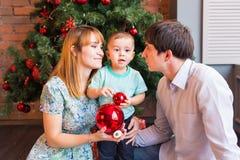 愉快的家庭母亲、父亲和使用在冬天的婴孩小孩为圣诞节假日 免版税库存图片