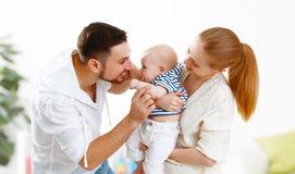 愉快的家庭母亲、父亲和儿子,婴孩在家 免版税库存图片
