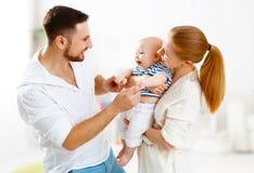 愉快的家庭母亲、父亲和儿子,婴孩在家 库存照片