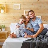 愉快的家庭母亲、父亲和儿童笑在床上 免版税库存照片